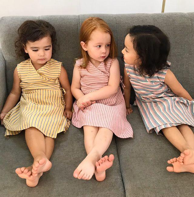 Three children sitting on a sofa, wearing Kokroma clothing